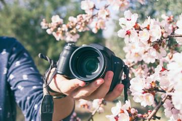 Mano de hombre sujetando una cámara digital entre flores de almendro