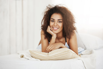 Beautiful happy african girl lying on pillow at home smiling looking at camera.