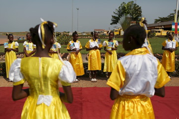 Girls await the arrival of Pope Francis at the international airport of the capital Bangui