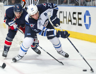 Winnipeg Jets Chris Thorburn is chased by New York Rangers Michael Del Zotto in their NHL hockey game in New York