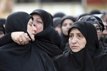 Relatives mourn the death of Ali Khadra, a man killed by a car bomb explosion that occurred on Thursday, in Beirut's southern suburbs