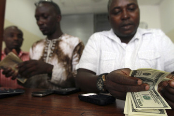 Employees count notes at a money exchange in Nigeria's commercial capital, Lagos