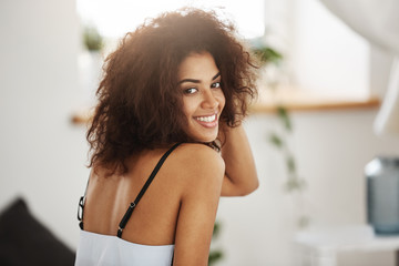 Portrait of beautiful african girl smiling looking at camera. Bedroom background.