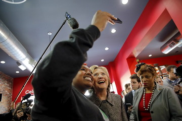 Democratic U.S. presidential candidate Hillary Clinton poses for a picture with a local resident during a campaign stop at Kuzzo's Chicken & Waffles restaurant in Detroit, Michigan