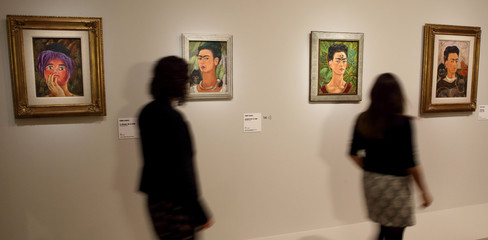 Visitors look at paintings by Mexican artist Frida Kahlo during the presentation of the exhibition 'Frida Kahlo/Diego Rivera, Art in Fusion' at the Musee de l'Orangerie in Paris