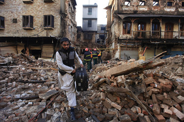 A man carries belongings recovered from a building which was burnt during Friday's sectarian clashes, in Rawalpindi