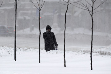 A man walks while talking on his mobile phone during snowfall in downtown Bucharest