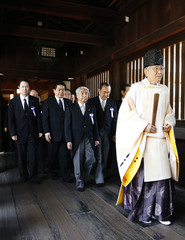 A group of lawmakers are led by a Shinto priest as they visit the Yasukuni Shrine in Tokyo