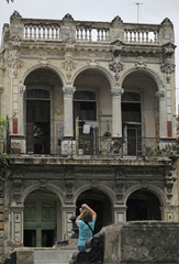 A woman takes a picture of a colonial-style house in Havana