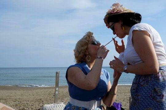 German pin-up Steiner and her friend Miranda, dressed in fifties-style outfits, light cigarettes as they attend the 22th Rockin' Race Jamboree International Festival in Torremolinos