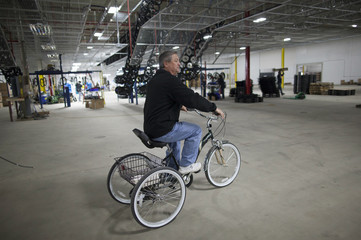 General manager Randy Donley uses a bike to travel through the plant at the new Bicycle Corporation of America plant in Manning