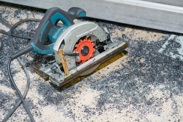 Circular electric saw on the concrete floor with iron powder