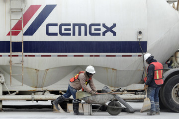 Workers stand in front of a trailer truck at a concrete plant of Mexican cement maker CEMEX, in Monterrey