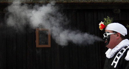 A man dressed as a chimney sweeper smokes during a traditional carnival in the east Bohemian village of Vesely Kopec