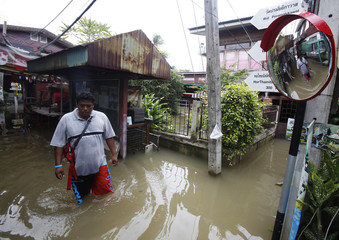 A man walks along a flooded street in Nonthaburi province