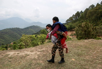 Nepal Army personnel carries an injured woman to a helicopter following Saturday's earthquake in Sindhupalchowk
