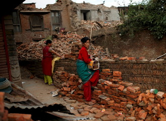 Women prepare to carry bricks from a collapsed house on the outskirts of Kathmandu