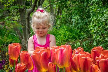 Little girl in garden of tulips experiencing Spring