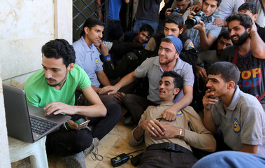 Civil Defence members, also known as the 'White Helmets', who have been nominated for the 2016 Nobel Peace Prize, gather around a laptop as they wait the announcemenet of the winner, in a rebel held area of Aleppo