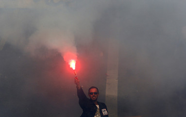 A worker holds a flare as he attend a demonstration against austerity plans which affect salaries and pensions in Marseille