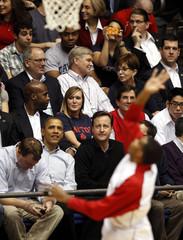 U.S. President Barack Obama sits next to British Prime Minister David Cameron during the NCAA men's college basketball tournament game in Dayton, Ohio