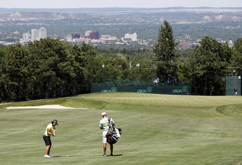 Yani Tseng of Taiwan hits her approach shot to the 10th green with the city in the background during a practice session for the U.S. Women's Open golf tournament at The Broadmoor in Colorado Springs