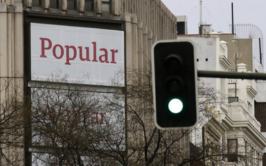 The logo of Popular bank can be seen near a green light at a Popular bank branch in Madrid, Spain