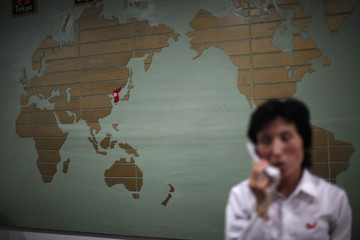 A world map with the Korea peninsula marked in red is seen as a hotel receptionist talks on the phone in Rason city