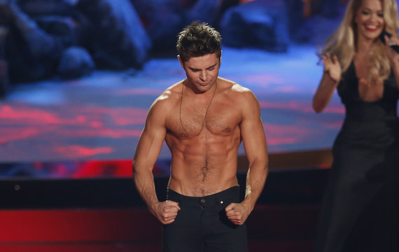 """Zac Efron poses after he threw off his shirt as he accepts the award for best shirtless performance for """"That Awkward Moment"""" at the 2014 MTV Movie Awards in Los Angeles"""