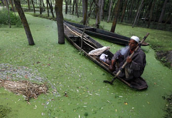 A Kashmiri man smokes a water pipe as he sits in his boat on the waters of Anchar Lake on a rainy day in Srinagar
