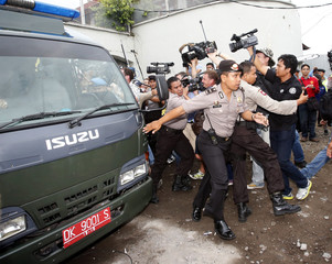 Police scuffle with members of the press as a van carrying convicted Australian drug trafficker Schapelle Corby leaves Kerobokan Prison in Bali