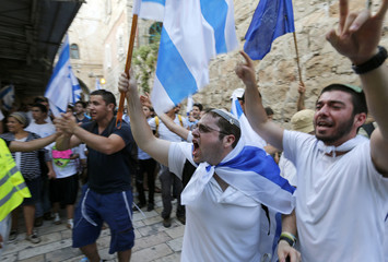 Israelis carry flags as they celebrate in Jerusalem's Old City during a parade marking Jerusalem Day