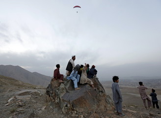 Afghans watch a paraglider in flight in Kabul