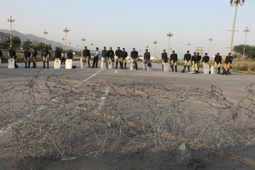 Policemen stand guard during a rally, by supporters of the Pakistan Tehreek-e-Insaf, against what the supporters say is vote rigging during the general election, in Islamabad