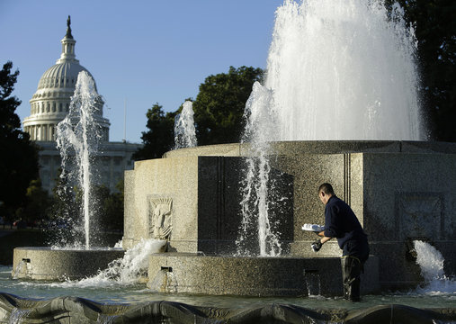 Pipe fitter Robert Kraft dispenses chlorine tablets in the Senate Garage Fountain near the US Capitol in Washington