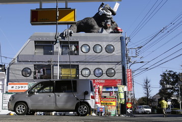 A gorilla statue is seen on top of a building in front of a Shell petrol station in Tokyo