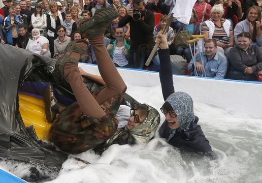 Participants fall after sliding down on a float along a chute to cross a pool of water and foam during a festival near the Siberian city of Krasnoyarsk