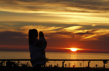 Woman takes a picture outside the Bolshoy Ice Dome as the sun sets on the Black Sea at the 2014 Sochi Winter Olympics
