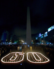 People light candles forming the number sixty during Earth Hour in front of the Buenos Aires' Obelisk