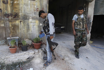 A Free Syrian Army member waters plants in Aleppo's Karm al-Jabal district