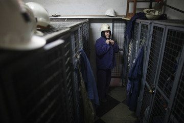 Covic buttons up her shirt before entering a coal mine in Breza
