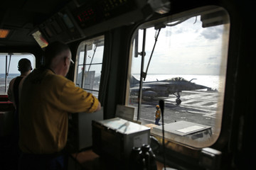 """A """"yellow dog"""" flight desk officer watches as a Rafale fighter jet prepares to take off France's Charles de Gaulle aircraft carrier on mission in the Gulf"""