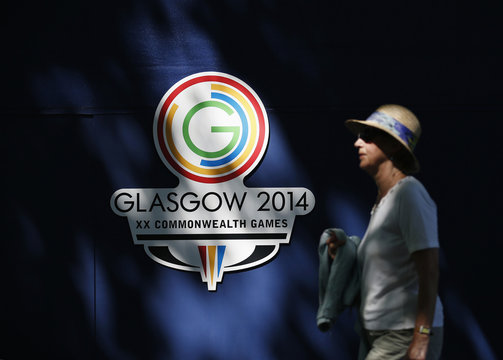 A spectator walks past Commonwealth Games logo at Kelvingrove Lawn Bowls Centre in Glasgow