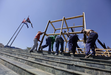 Workers move a wooden frame in Santiago de Cuba's Revolution Square as they assemble an altar