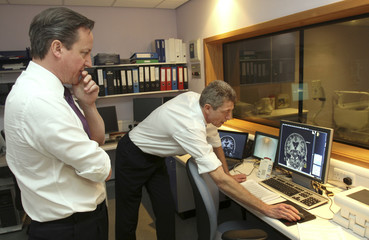 Britain's Prime Minister David Cameron looks at a brain scan as he stands with professor Nick Fox at the National Hospital for Neurology and Neurosurgery in London