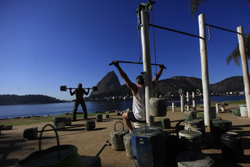 Men work out using improvised weights with Sugar Loaf Mountain in the background, in Rio de Janeiro
