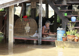 A local Thai woman sits carving wood products on a table as the rising flood water invade her home in Ayutthaya province