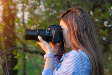 Beautiful young girl taking pictures in the forest. The girl with the camera. Tourist. Sunset.