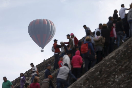 A hot air ball balloon floats past while people stand in line to climb the Pyramid of the Sun and welcome the spring equinox in the pre-hispanic city of Teotihuacan, on the outskirts of Mexico City