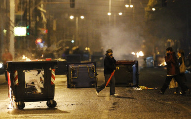 People walk past burning garbage bins after a rally in Athens